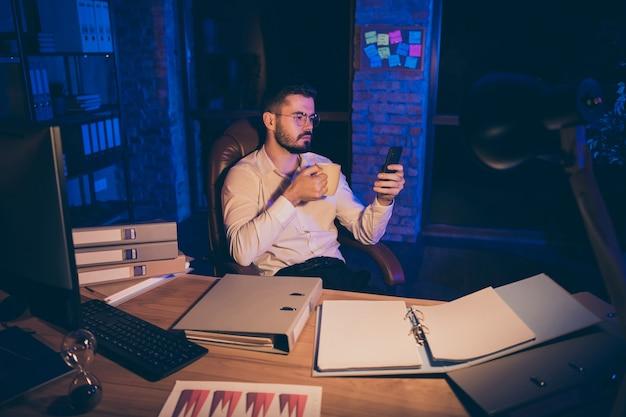 Doordachte man houdt telefoon mok koffie drinken