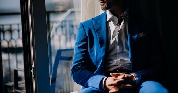 Doordachte man in blauwe pak zit op de vensterbank