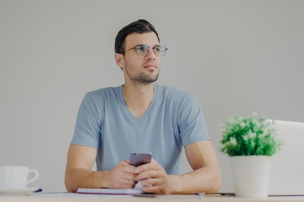 Doordachte mannelijke freelancer werkt op afstand op een laptop, kijkt pensively en houdt moderne mobiele telefoon