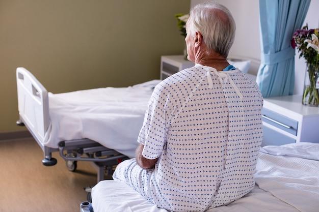Doordachte mannelijke senior patiënt zitten in de afdeling
