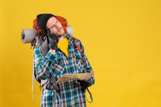 Doordachte mannelijke toerist met leren handschoenen en rugzak met kaart