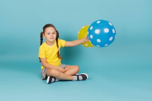 Doordachte meisje houdt ballonnen in haar uitgestrekte hand en zit op de vloer