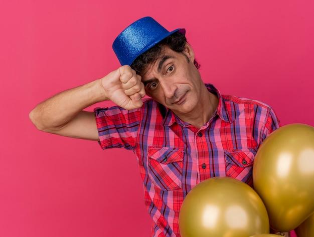 Doordachte middelbare leeftijd blanke feestmens met feestmuts staande achter ballonnen hoofd aanraken met vuist kijken kant geïsoleerd op karmozijnrode achtergrond