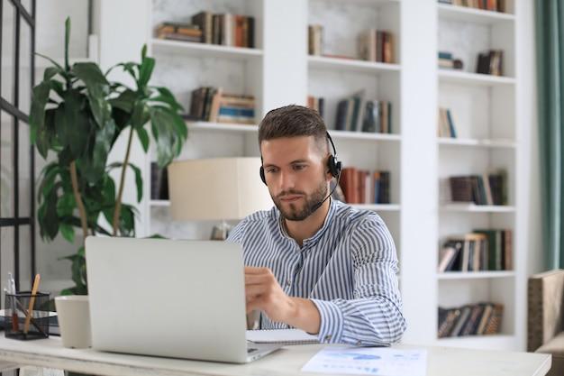 Doordachte moderne zakenman die met laptop werkt terwijl hij op kantoor zit.