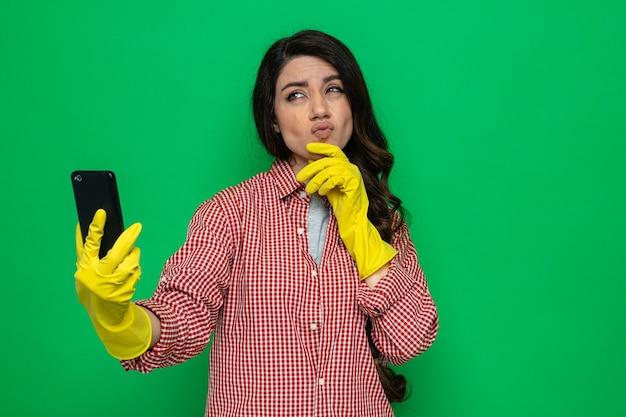 Doordachte, mooie blanke schonere vrouw met rubberen handschoenen die de hand op haar kin legt en de telefoon vasthoudt