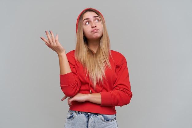 Doordachte mooie blonde jonge vrouw met sproeten in rode hoodie wegkijken en lege ruimte op palm over grijze muur te houden