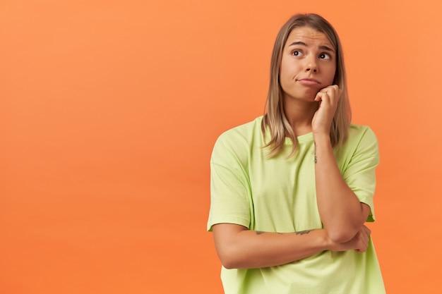 Doordachte mooie jonge vrouw in gele t-shirt houdt handen gevouwen en denkt geïsoleerd over oranje muur