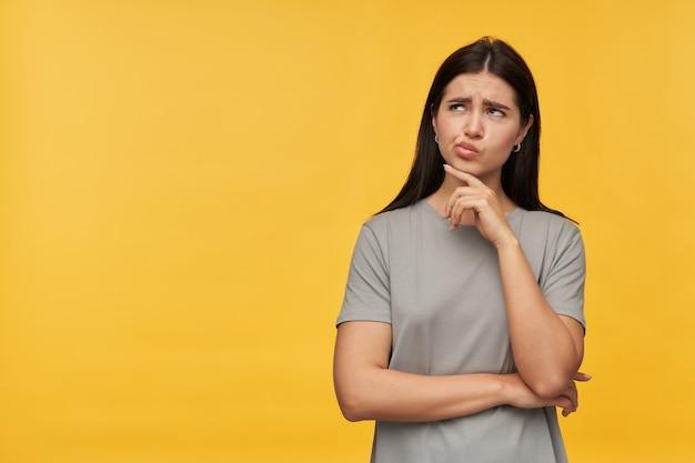 Doordachte mooie jonge vrouw met donker haar in grijze t-shirt die haar kin aanraakt en wegkijkt naar de lege ruimte over gele muur