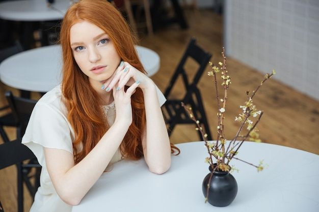 Doordachte mooie jonge vrouw zitten in café