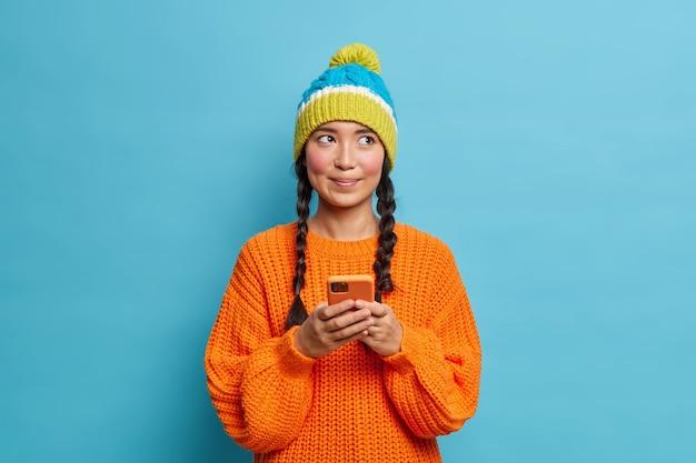 Doordachte mooie tienermeisje houdt mobiele telefoon vast en stuurt sms-berichten denkt welk antwoord te geven leest opmerkingen onder haar bericht in sociale netwerken gekleed in winterkleren geïsoleerd op blauwe muur