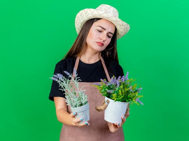Doordachte mooie tuinman meisje in uniform dragen tuinieren hoed bedrijf en kijken naar bloem in bloempot geïsoleerd op groen