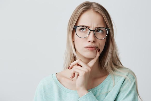 Doordachte mooie vrouw heeft lang blond haar met stijlvolle bril, kijkt peinzend opzij, plant iets in de komende weekenden, poseert tegen de blinde muur. verbaasd vrouwtje