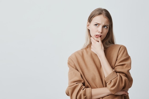 Doordachte mooie vrouw met lang blond haar, kijkt naar boven met peinzende uitdrukkingen, plant iets, vormt tegen blinde muur. ernstige geconcentreerde vrouwelijke vinger op kin houden