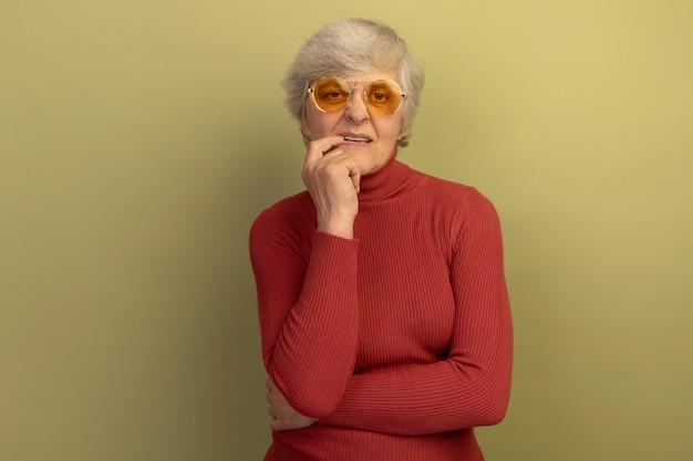 Doordachte oude vrouw met een rode coltrui en een zonnebril die de vinger op de lip legt