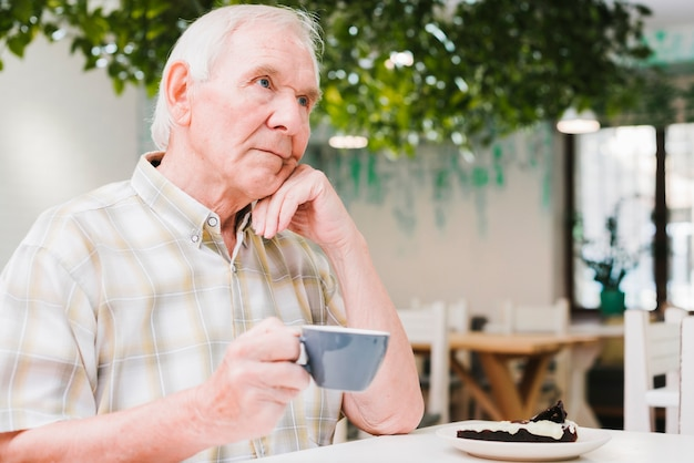 Doordachte oudere man het drinken van thee