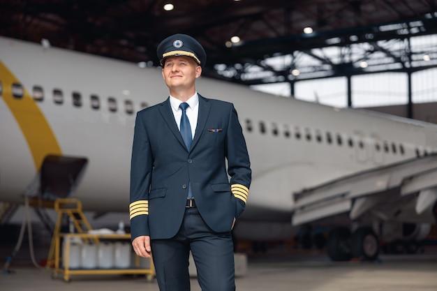 Doordachte piloot in uniform die wegkijkt, staande voor een groot passagiersvliegtuig in de hangar van de luchthaven. vliegtuigen, beroep, transportconcept