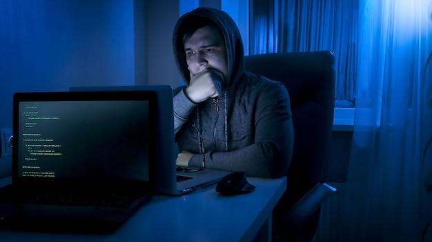 Doordachte programmeur in kap die op laptopscherm kijkt terwijl hij 's nachts werkt