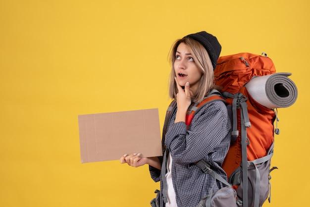 Doordachte reiziger vrouw met rode rugzak met karton holding