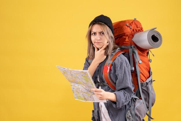 Doordachte reiziger vrouw met rugzak met kaart