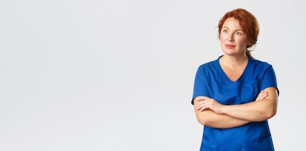 Doordachte roodharige verpleegsterarts of vrouwelijke arts in scrubs die linkerbovenhoek kijkt met intrig...