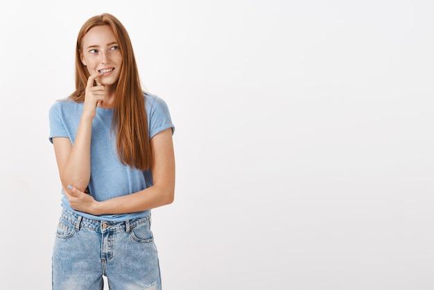 Doordachte, rustige en vrolijke aantrekkelijke roodharige vrouw met sproeten bijtende vinger starend naar de rechterbovenhoek tijdens het denken of herinneren