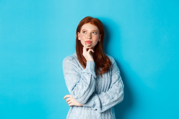 Doordachte schattige vrouw met rood haar, kijkend naar het logo in de linkerbovenhoek en denkend, iets voorstellend, staande over een blauwe achtergrond.