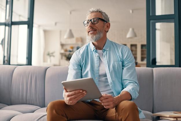 Doordachte senior man die digitale tablet gebruikt en wegkijkt met een glimlach terwijl hij thuis op de bank zit