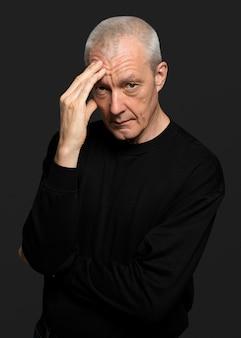 Doordachte senior man in een zwart t-shirt met lange mouwen