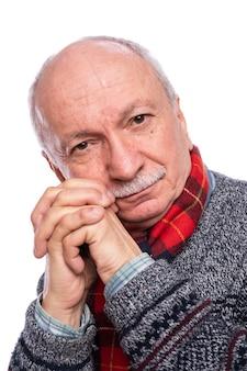 Doordachte senior man poseren in studio op witte achtergrond