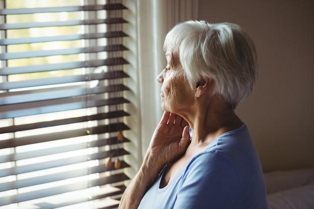 Doordachte senior vrouw kijkt uit raam thuis