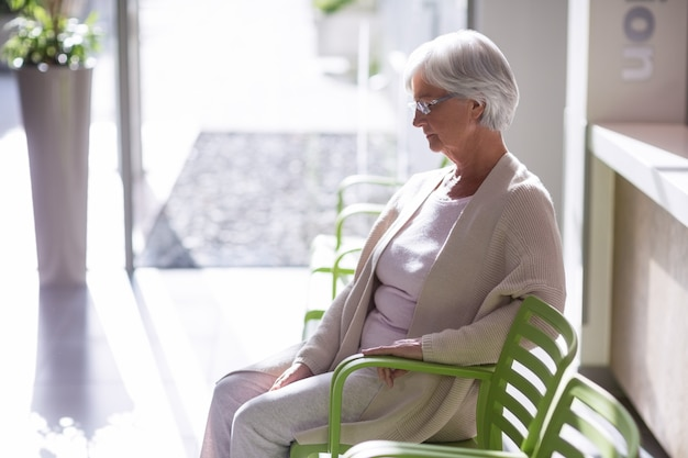 Doordachte senior vrouw zittend op een stoel