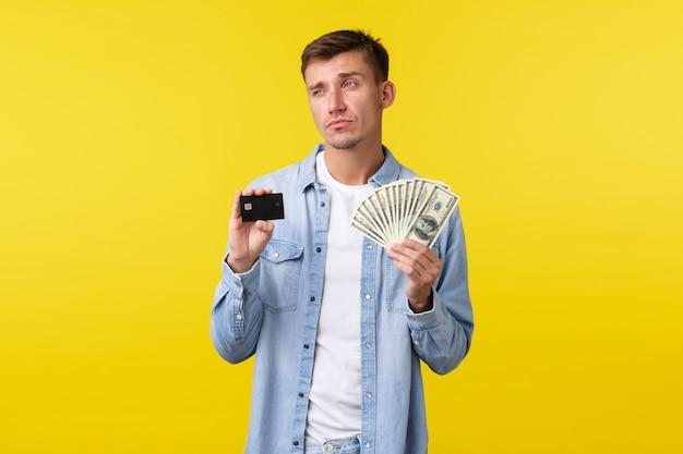 Doordachte serieuze blonde knappe man die creditcard en geld toont, wegkijkt, denkend hoe geld te investeren, nadenken over wat kopen tijdens het winkelen, staande gele achtergrond.