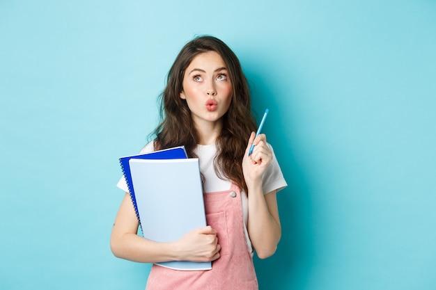 Doordachte slimme vrouwelijke student die een pen vasthoudt en een idee heeft, peinzend opkijkt, notitieboekjes draagt, staande tegen een blauwe achtergrond.