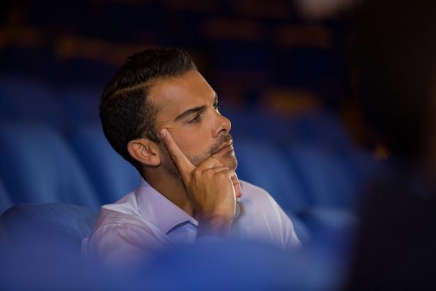 Doordachte stafmedewerker luisteren naar toespraak op conferentiecentrum