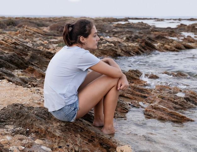 Doordachte tienermeisje zittend op een klif aan zee met benen in het water bij zonsondergang en recht kijken, gekleed in blauw t-shirt en jeans shorts, zijaanzicht. t-shirtmodel
