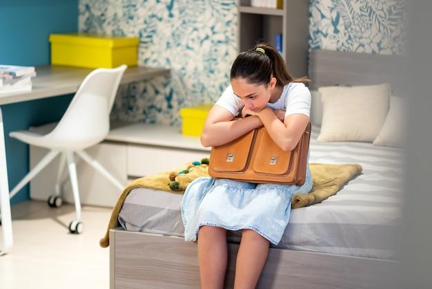 Doordachte tienerschoolmeisje in vrijetijdskleding met schooltas die zich eenzaam voelt tijdens de periode van sociale afstand terwijl ze thuis in de slaapkamer zit