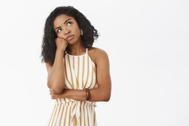 Doordachte triest en verveeld afro-amerikaanse vrouw in gestreepte gele overall leunend hoofd op vuist kijken rechterbovenhoek denken
