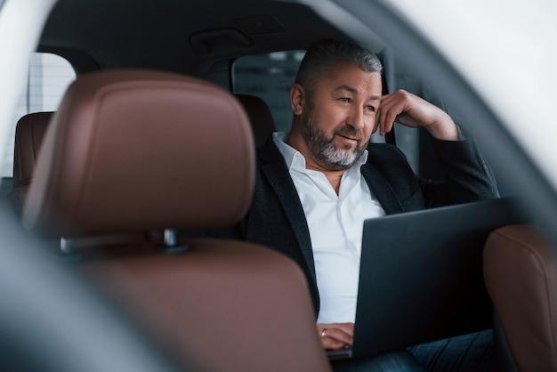 Doordachte uitstraling. werken aan een achterkant van de auto met behulp van zilverkleurige laptop. senior zakenman