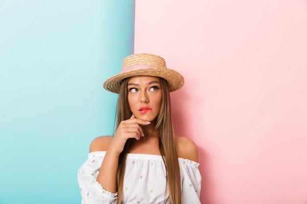 Doordachte verwarde jonge mooie vrouw poseren geïsoleerd dragen hoed.