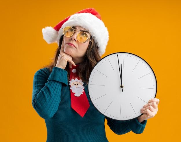 Doordachte volwassen blanke vrouw in zonnebril met kerstmuts en santa stropdas houdt klok en zet de vinger op de kin opzoeken geïsoleerd op oranje muur met kopie ruimte