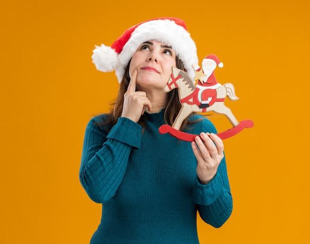 Doordachte volwassen blanke vrouw met kerstmuts legt vinger op kin en houdt santa op schommelpaard decoratie opzoeken geïsoleerd op een oranje achtergrond met kopie ruimte