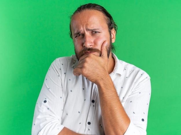 Doordachte volwassen knappe man die de hand op de kin houdt en naar de camera kijkt die op de groene muur is geïsoleerd