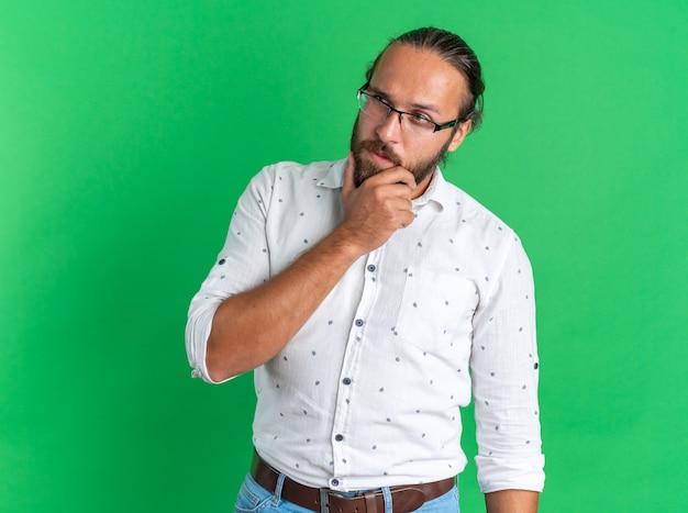 Doordachte volwassen knappe man met een bril die de hand op de kin houdt en naar de kant kijkt die op de groene muur is geïsoleerd