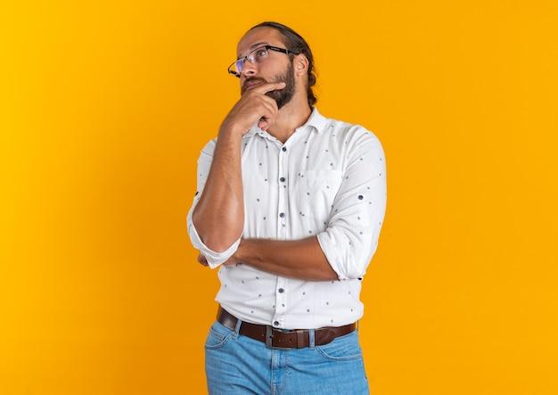 Doordachte volwassen knappe man met een bril die de hand op de kin houdt en naar de kant kijkt die op een oranje muur met kopieerruimte is geïsoleerd