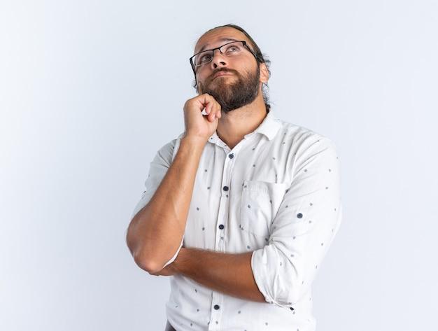 Doordachte volwassen knappe man met een bril die de hand op de kin houdt en omhoog kijkt geïsoleerd op een witte muur
