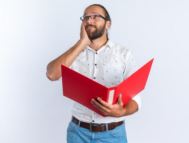 Doordachte volwassen knappe man met een bril die de hand op het gezicht houdt en een open map vasthoudt die naar de zijkant kijkt die op een witte muur is geïsoleerd