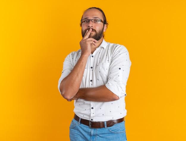 Doordachte volwassen knappe man met een bril die de vingers op de lippen houdt en naar de camera kijkt die op een oranje muur met kopieerruimte is geïsoleerd