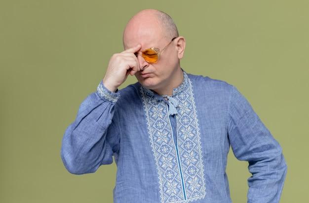 Doordachte volwassen man in blauw shirt met een zonnebril die zijn hand op zijn voorhoofd legt