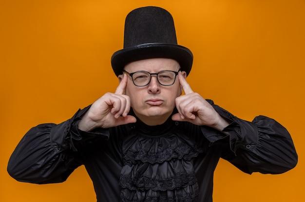 Doordachte volwassen man met hoge hoed en bril in zwart gotisch shirt die vingers op zijn slapen legt en kijkt