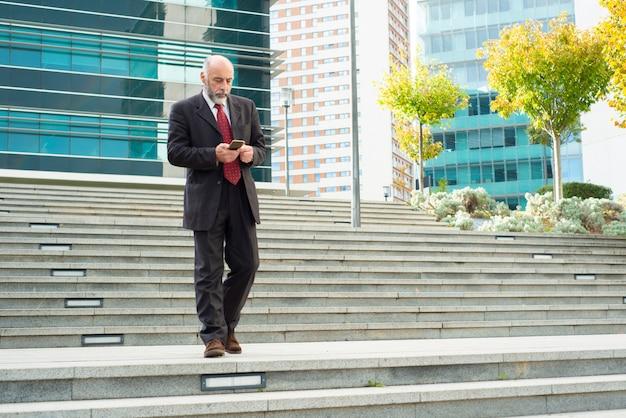 Doordachte volwassen man met telefoon tijdens het lopen naar beneden op de trap